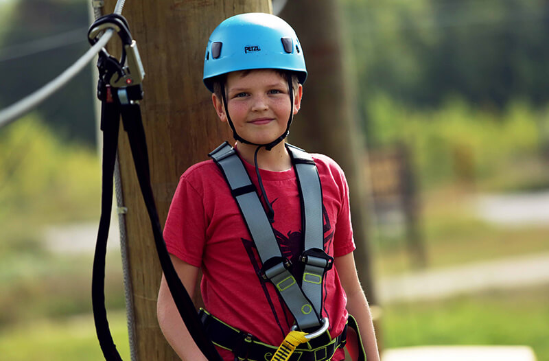 Smiling boy on the adventure park course