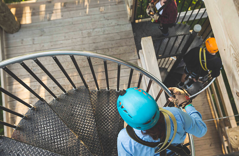 Man walks up spiral staircase as he prepares to zipline