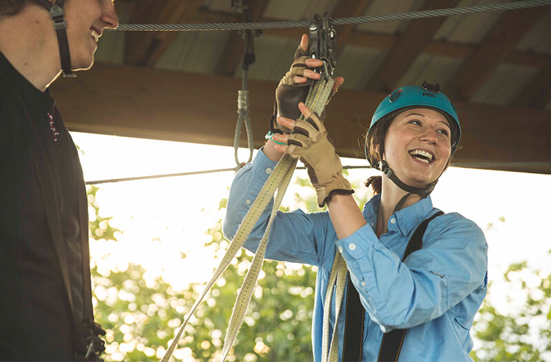 Women happily prepares the zipline