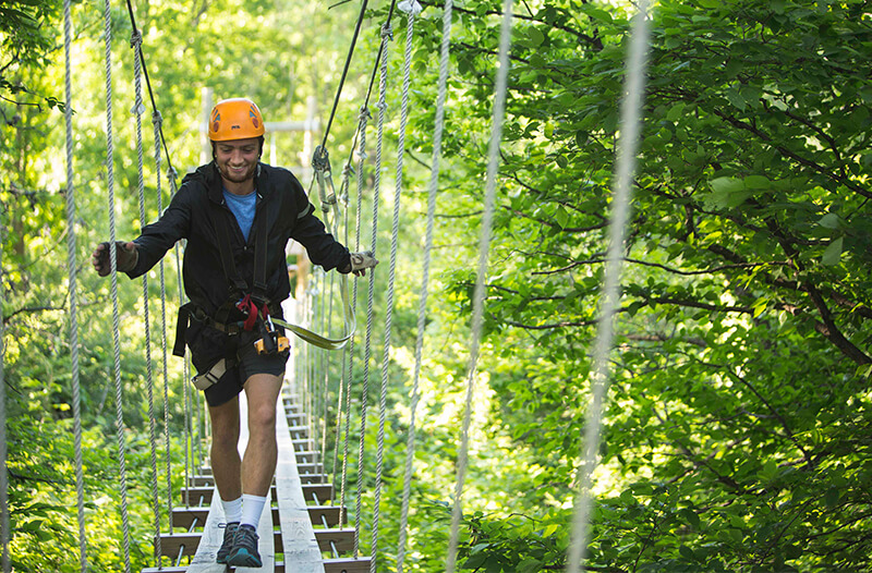 Man looks down while running across the kerfoot suspension bridge