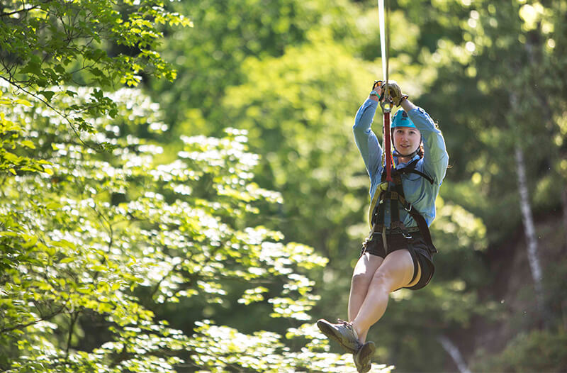 Girl zipliner flies through the trees on a zipline
