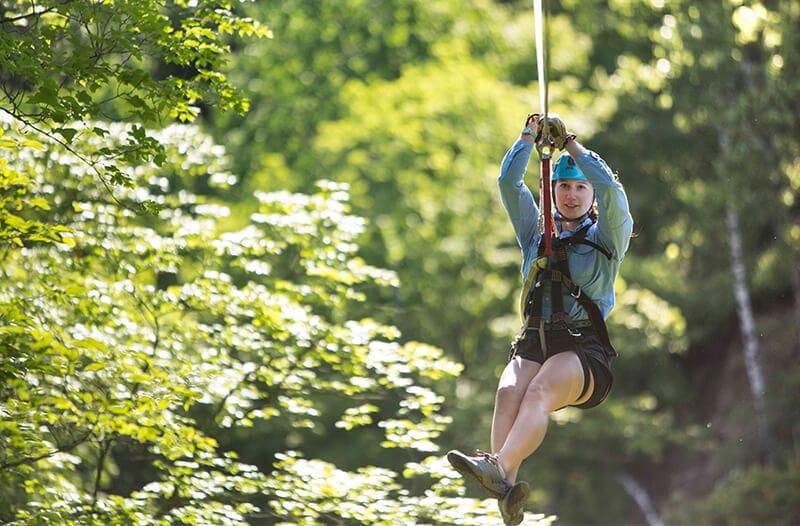 Minnesotas 1 zipline tour twin cities zip line kerfoot canopy tour girl zipliner flies through the trees on a zipline solutioingenieria Choice Image