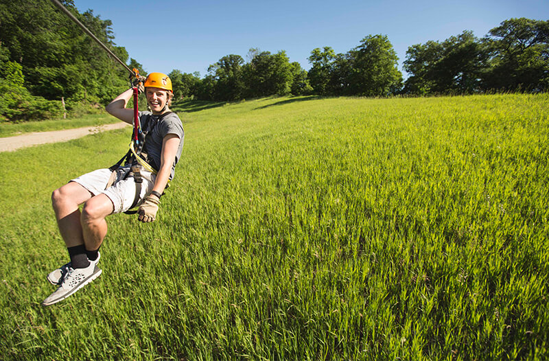 Laughing zipliner flies over lush green field