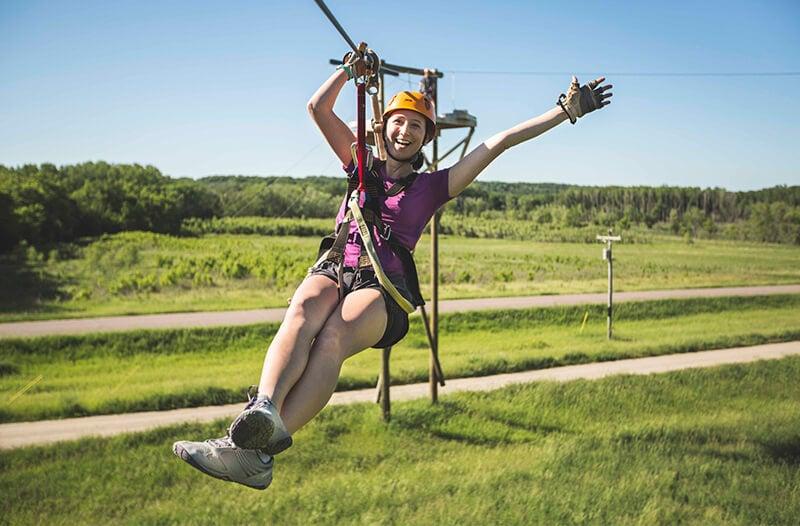 Happy zipliner flies over field