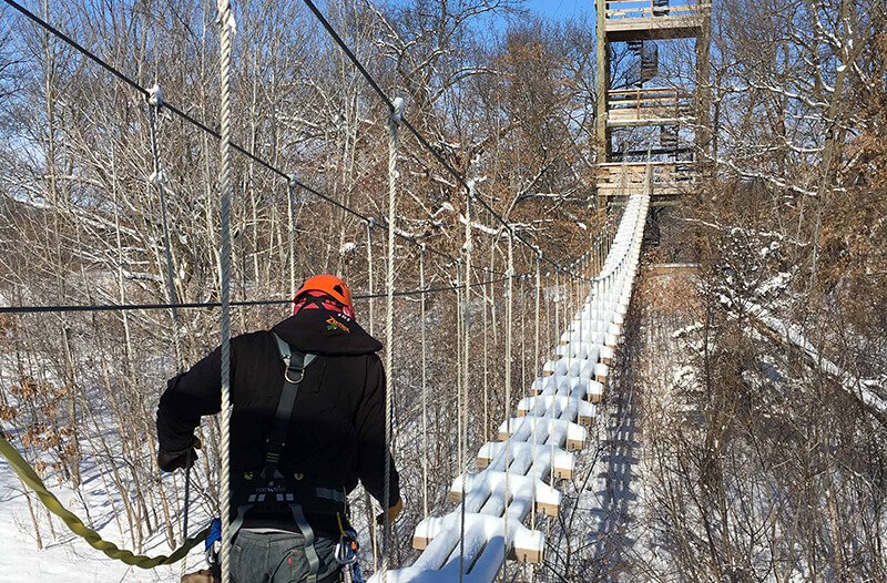 Man walks across suspension bridge with snow on it