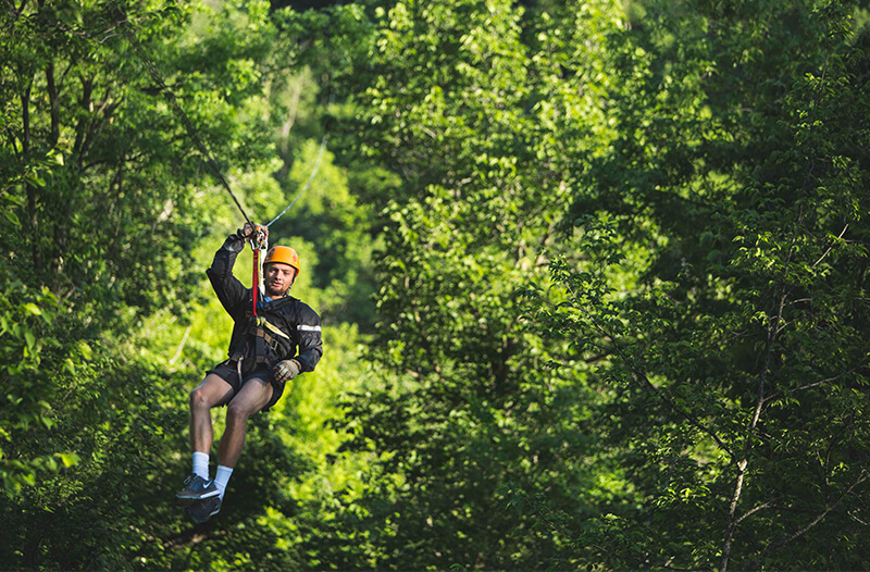 Man Zip lining through the trees