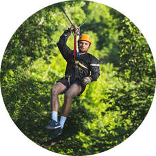 Young man zip lines in a forest