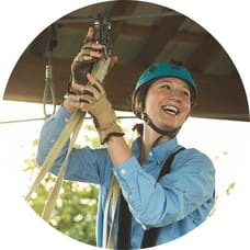 Smiling young woman attaches a zipline harness to a zipline