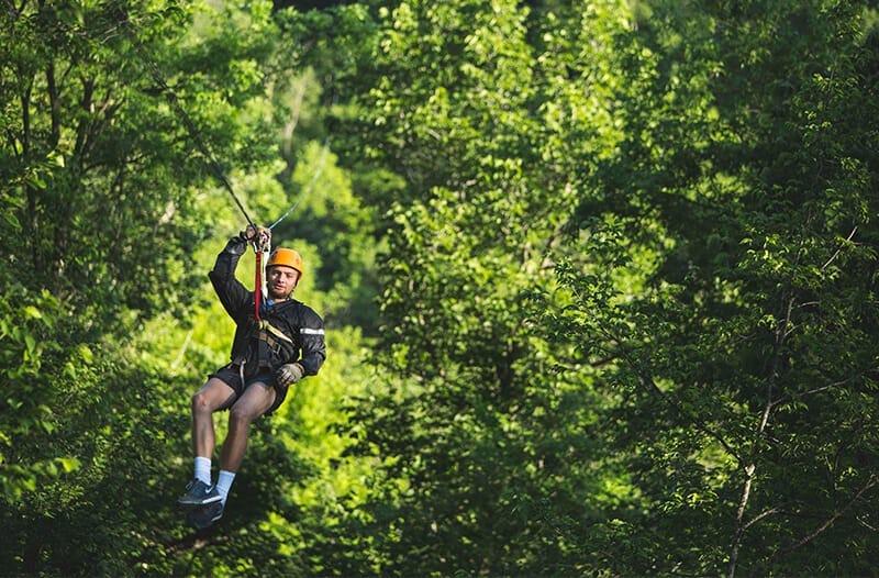 Man ziplines through a forest