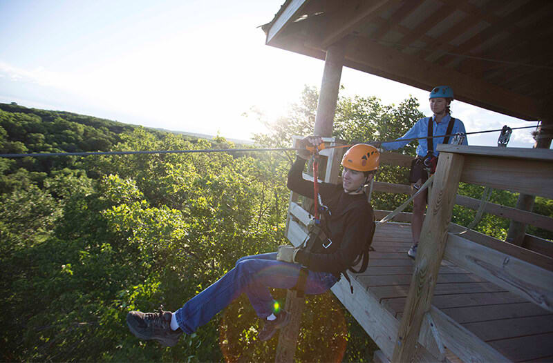 Young man leaves a ziplining platform