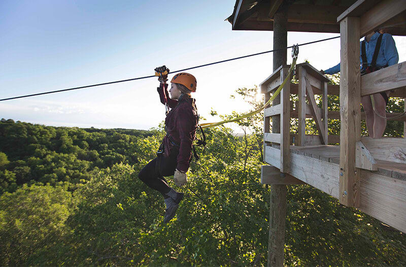A young woman rides a zipline above a forest
